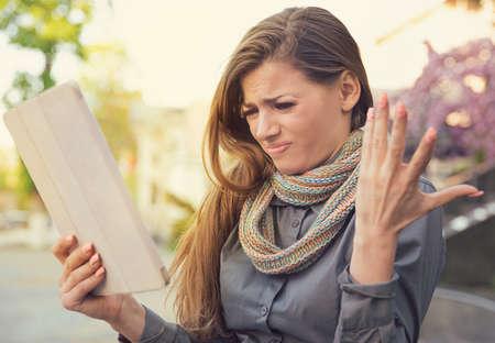 mujer joven que mira frustrado y desesperado siendo la sensación de la tableta con la aplicación de la aplicación agradable en la calle