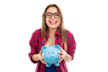 Young happy teen woman in glasses holding blue piggybank with savings for future and smiling at camera isolated on white background 스톡 콘텐츠