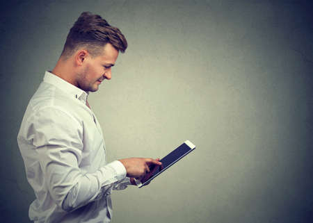 Content casual guy in white shirt browsing modern tablet enjoying new device standing on gray. 스톡 콘텐츠