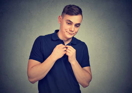 Young casual man looking shy and quiet on gray background holding hands in hesitation Standard-Bild