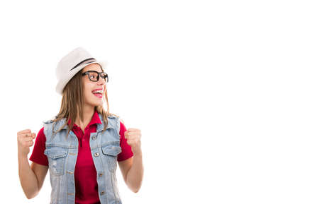 Casual young woman in hat and glasses with fists up screaming feeling excited looking super thrilled to the side isolated on white background Stockfoto