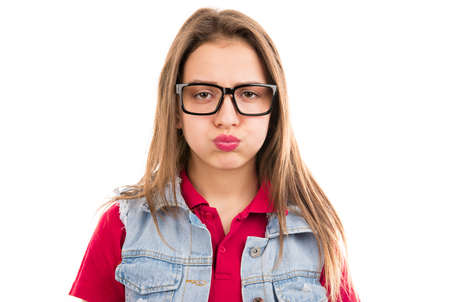 Young grumpy woman in glasses looking unhappy and puffing cheeks in disagreement isolated on white background