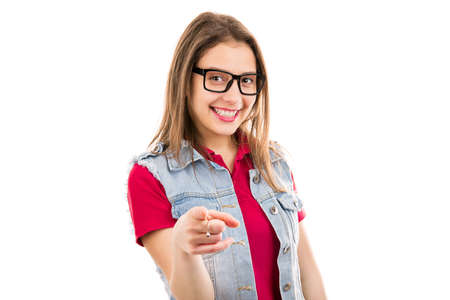 Pretty modern young woman in eyeglasses pointing at camera in selection making choice isolated on white background