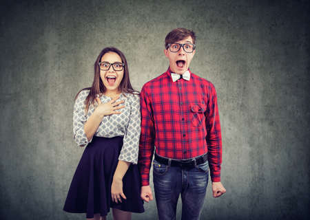 Young modern man and woman in eyeglasses screaming with astonishment and looking at camera on gray background Imagens