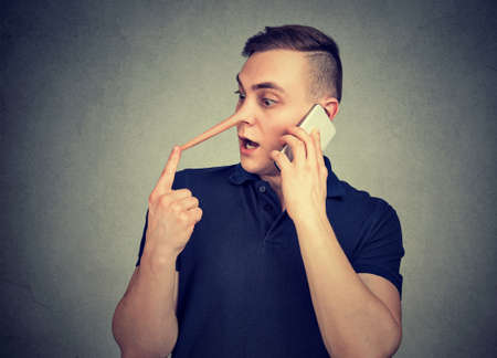 Young hypocritic man with long nose talking on smartphone and lying expressively on gray background.