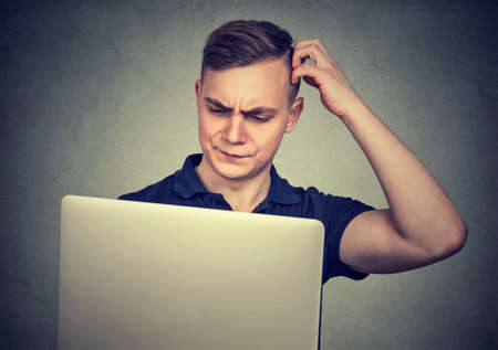 Young casual man looking perplexed while using laptop having difficulties with device.