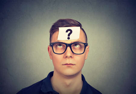 thinking man with question mark on gray wall background Stock Photo