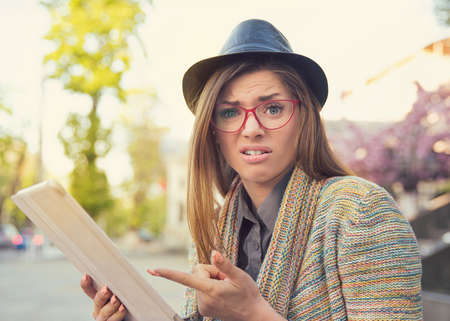 Young hipster woman in hat and eyeglasses holding tablet on street and looking stressed and offended pointing at device
