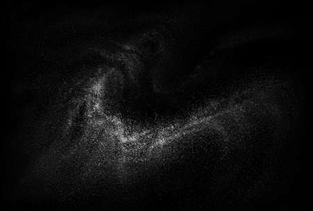 Freeze motion of white powder exploding, isolated on black background. Abstract design of white dust cloud.
