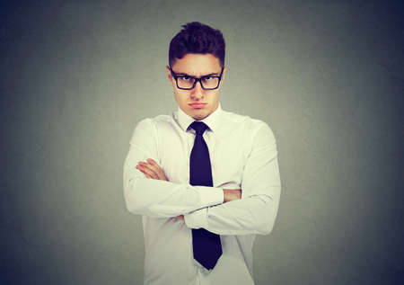 Frowning angry business man looking at camera on gray wall background