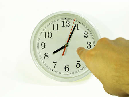 tardiness: A man pointing to the clock showing a little past 8. Stock Photo