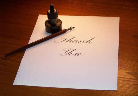 pluma de escribir antigua: Escribir una nota de agradecimiento con caligraf�a en la tabla. Foto de archivo
