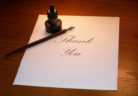 Writing a thank you note with calligraphy set on table.