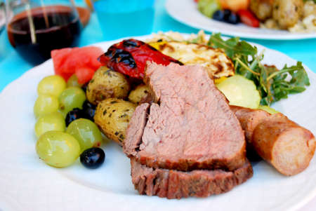Picture focused on the center of tri-tip with colorful food around.