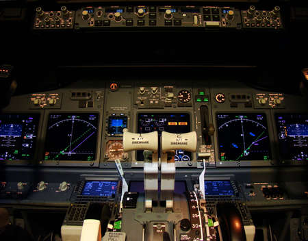 levers: Flight deck of a modern airliner at night. Stock Photo