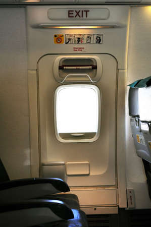 Emergency exit door. Passenger cabin of a commercial airliner. Stock Photo