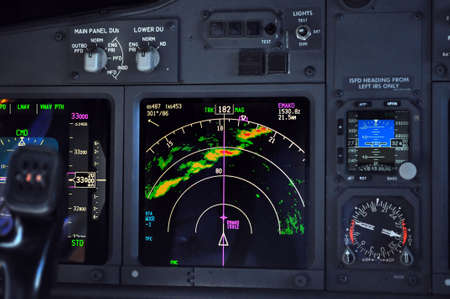 airborne vehicle: Aircraft instrument panel. Commercial airliner approaches line of thunderstorms at 33000 feet