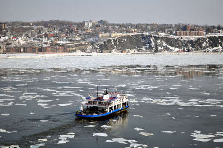 departing: Transportation: Ferry boat crossing river in winter