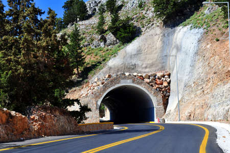 curve road: Mountain road passing through a tunnel in the island of Crete.