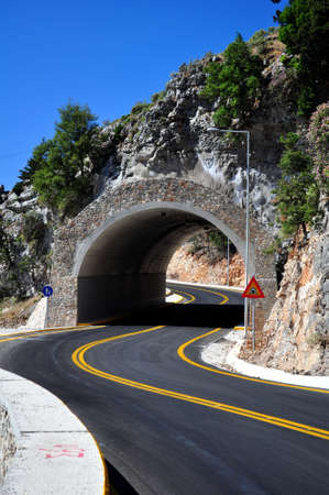 trafic: Mountain road passing through a tunnel.