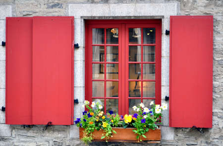 Old window with colorful flowers in Quebec City, Canada.