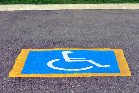incapacitated: Handicapped reserved parking sign painted on pavement Stock Photo