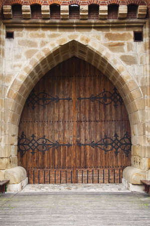 arc: Gothic wooden door at medieval fortification in Krakow, Poland.