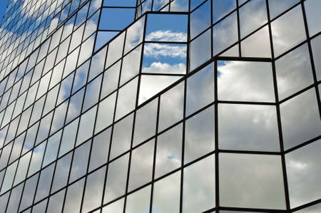 office building exterior: Modern glass office building with clouds and sky reflections. Stock Photo