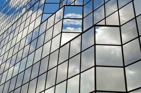 edificio corporativo: Vidrio moderno edificio de oficinas con nubes y reflexiones de cielo.
