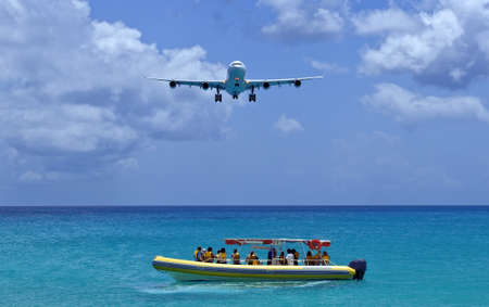Passenger airplane flies over boat on approach to Caribbean airport. Stock fotó
