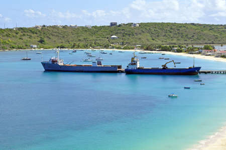 Two ships offloading cargo at caribbean port.