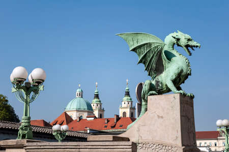 Dragon Bridge with St Nicholas Cathedral in the background, in Ljubljana, Slovenia