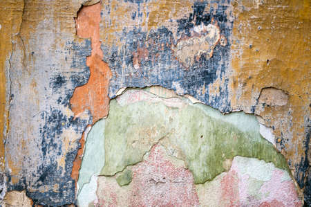 Old damaged wall with layers of colors.