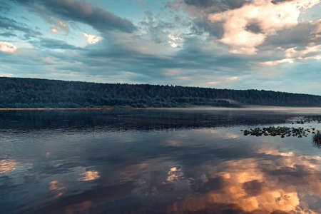 Reflection of clouds in the calm water of the river with a wooded shore