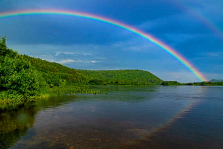 Rainbow over the river with reflection in the water against the cloudy sky