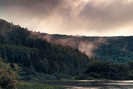 The fog comes down from the mountains overlooking the tops of the trees in the forest on the river bank.