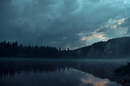 Night river on different banks of which there is a gloomy forest and rocks. Banco de Imagens