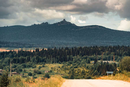 A mountain road in the foreground, leaving in the distance, where on the horizon you can see a mountain with a forest. Banco de Imagens