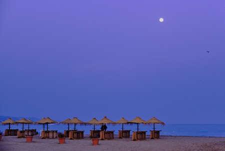 moon in the sky with umbrellas on the beach at dusk in malaga beach Foto de archivo