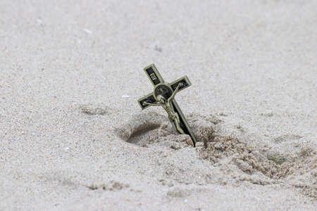 Jesus Christ on a cross buried in the sand Standard-Bild