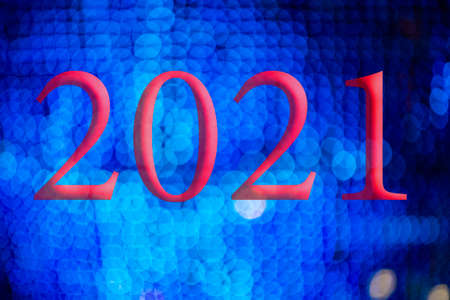 Text with the year number 2021 with a background of bright blue lights out of focus with Bokeh effect. Happy New Year 2021.