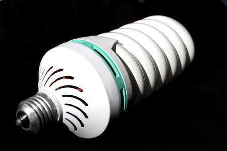 watts: Big coiled daylight bulb Isolated on a black background  Bulb specifications is 23 cms in lenght, 8 cms diameter, 220 volts and 105 watts   Stock Photo