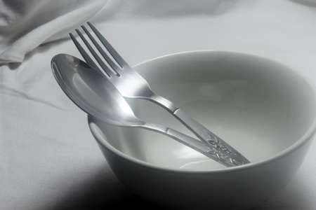 utencils: Stainless steel spoon and fork in an empty ceramic bowl Stock Photo