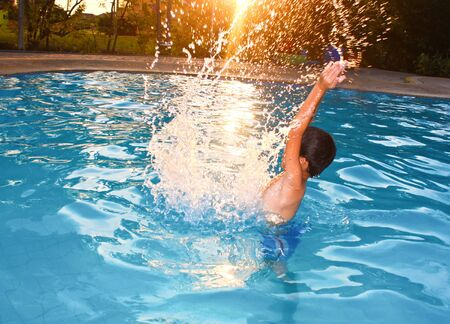 Asian young boy splashing in water as the sun glowing its light. photo