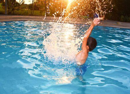 its a boy: Asian young boy splashing in water as the sun glowing its light.