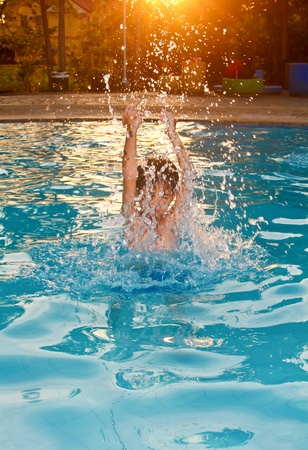 Boy splashing water in a private pool full of enjoyment. photo