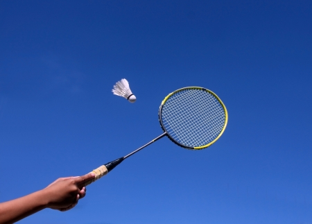 A badminton racquet and a shuttlecock against the clear blue sky. photo