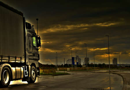 Truck driving trough stormy weather in dramatic HDR urban outskirts on wet asphalt