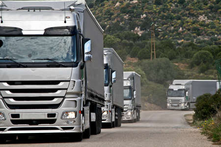 Caravan of silver trucks approacinh at perspectyve to viewer