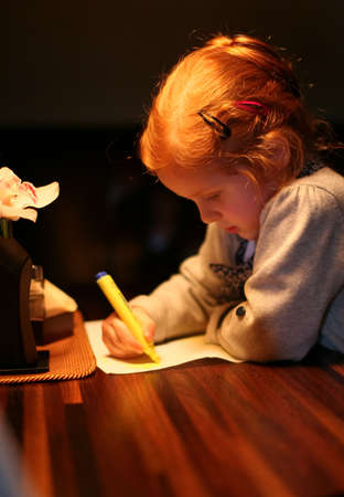 Little cute redhead girl painting on the table with yellow pen on the dark photo